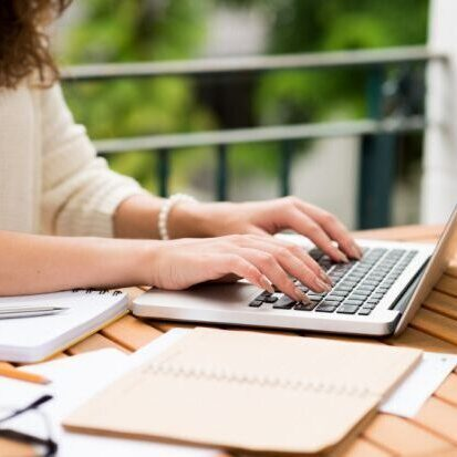lady writing on computer with notepad beside her at Whisenhunt Communications PR and Marketing Firm
