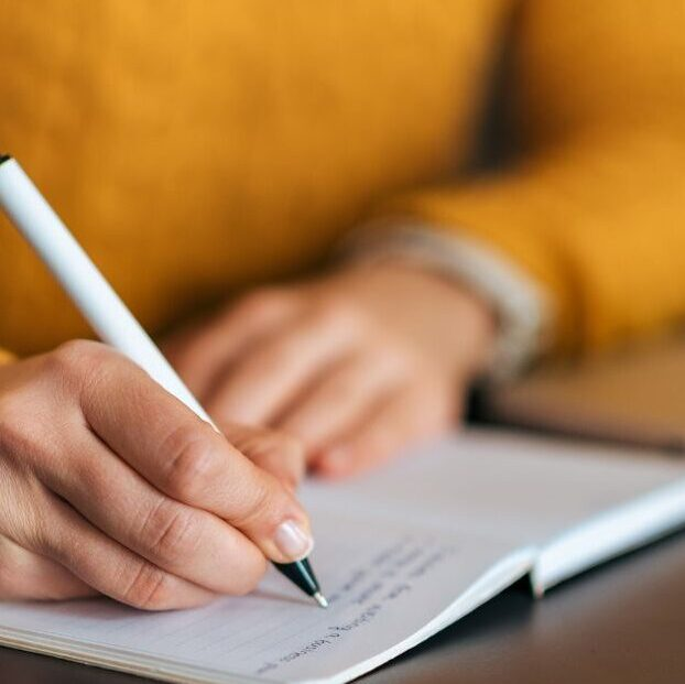 writing with a pen and notepad at Whisenhunt Communications PR and Marketing Firm